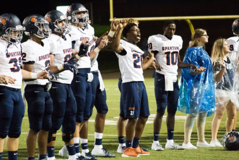 KJ Leggins leads singing the Alma Mater after winning the game.