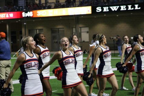 The cheer team performs a chant at a home football game.
